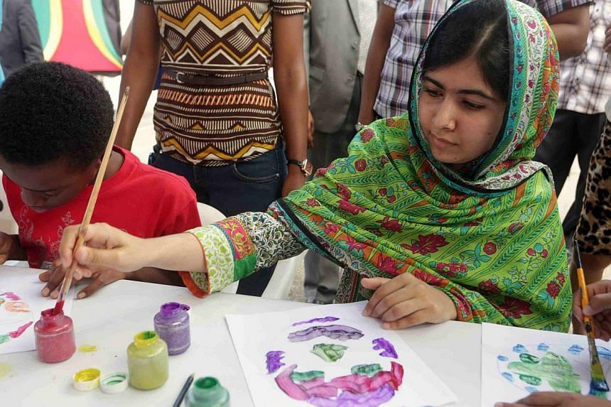 Pakistani schoolgirl activist Malala Yousafzai paints at an art workshop during a visit to the Emancipation Village at Queen's Park Savannah, Port-of-Spain on July 31, 2014. -- PHOTO: REUTERS