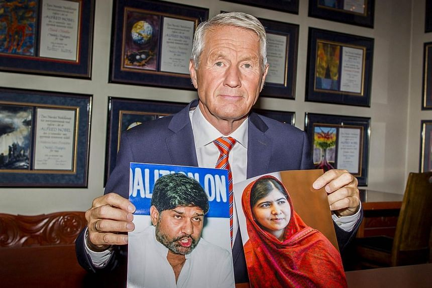 The chairman of the Norwegian Nobel Committee, Thorbjorn Jagland, poses with pictures of Pakistani education activist Malala Yousafzai (right) and Kailash Satyarthi (left), Indian anti-child labour activist, who have been awarded the Nobel Peace Priz