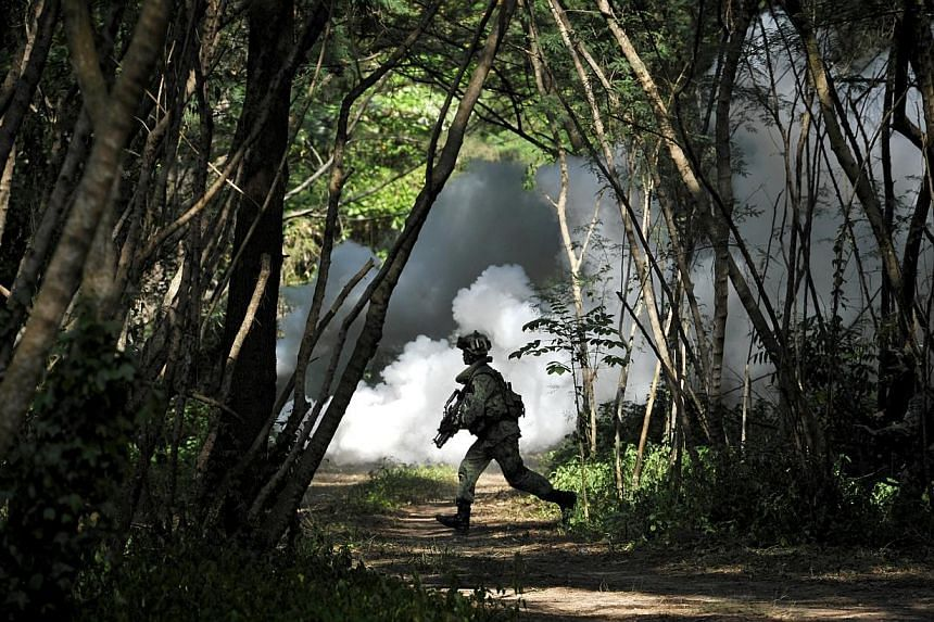 A soldier running with his weapon during the Singapore Armed Forces (SAF) Readiness Exercise at Pulau Sudong. The Singapore Armed Forces (SAF) will conduct military exercises in Seletar, Marsiling, Jalan Bahar, Neo Tiew, Lim Chu Kang, Jalan Kwok Min,