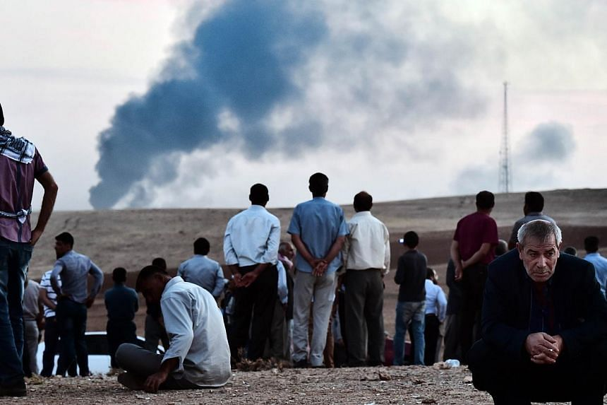 Kurdish people stand on a hill at the Turkish-Syrian border as smoke rises from the Syrian town of Ain al-Arab, known as Kobane by the Kurds, in the southeastern village of Mursitpinar, Sanliurfa province, on Oct 9, 2014.Islamic State group mil
