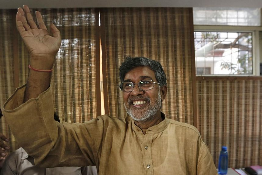 Indian children's right activist Kailash Satyarthi waves to the media at his office in New Delhi on Oct 10, 2014. Mr Satyarthi, 60, and Malala Yousafzai, 17, from Pakistan, were jointly awarded the Nobel Peace Prize on Friday. -- PHOTO: REUTERS