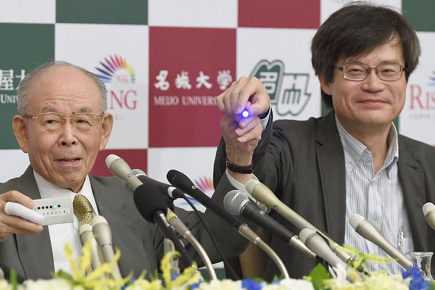 Meijo University Professor Isamu Akasaki (left) and Nagoya University Professor Hiroshi Amano (right) hold a prototype (left) and a new blue light-emitting diode (LED) during a press conference at Nagoya University in Nagoya, central Japan on Oct 10,