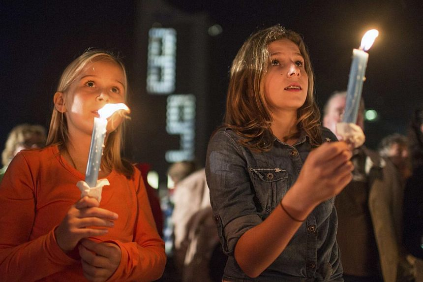 Girls hold candles at Augustusplatz square in front of a building showing the number 89 in Leipzig on Oct 9, 2014. Celebrations on Thursday marked the 25th anniversary of a historic demonstration in the eastern German city, when 70,000 East German ci