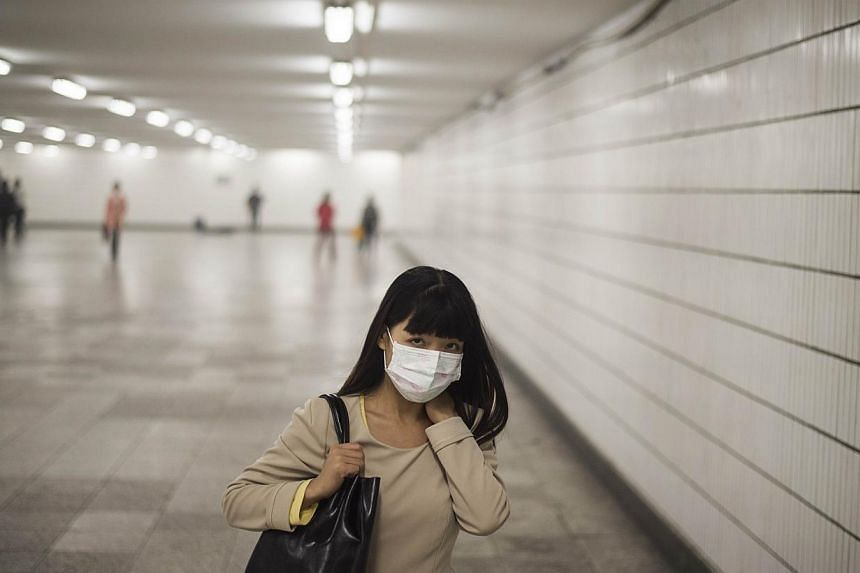 A woman wears a face mask in Beijing amid heavy smog on Oct 10, 2014. -- PHOTO: AFP