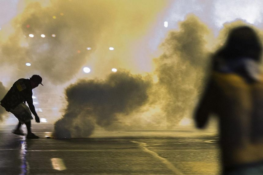 A protester reaches down to throw back a smoke canister as police clear a street after the passing of a midnight curfew meant to stem ongoing demonstrations in reaction to the shooting of Michael Brown in Ferguson, Missouri on Aug 17, 2014.An i