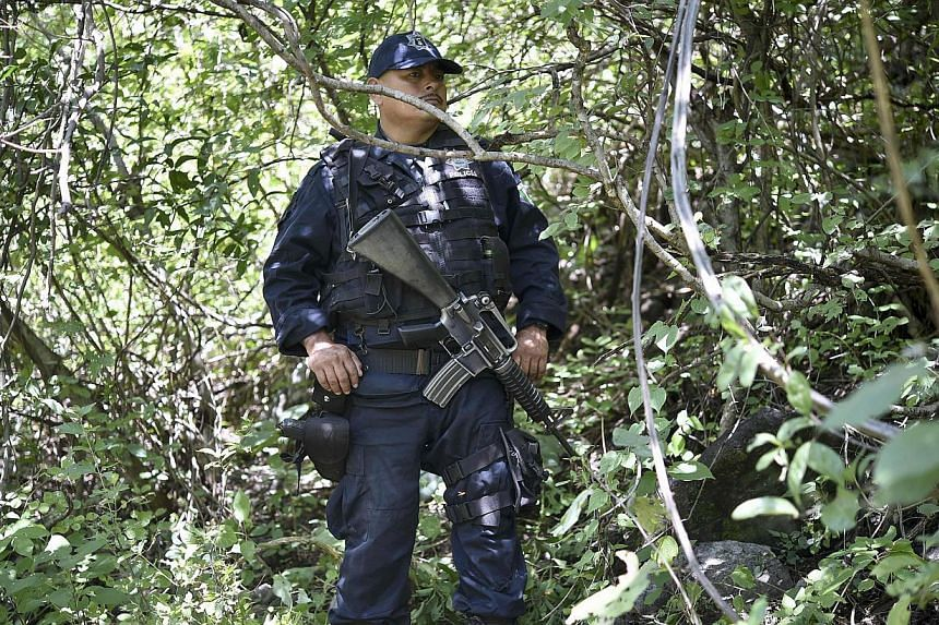 A state police officer stands guard near a mass grave that was found days ago at the foot of a hill outside of Iguala, Guerrero state, Mexico on Oct 09, 2014.Mexican authorities have found four new mass graves in the investigation into the disa