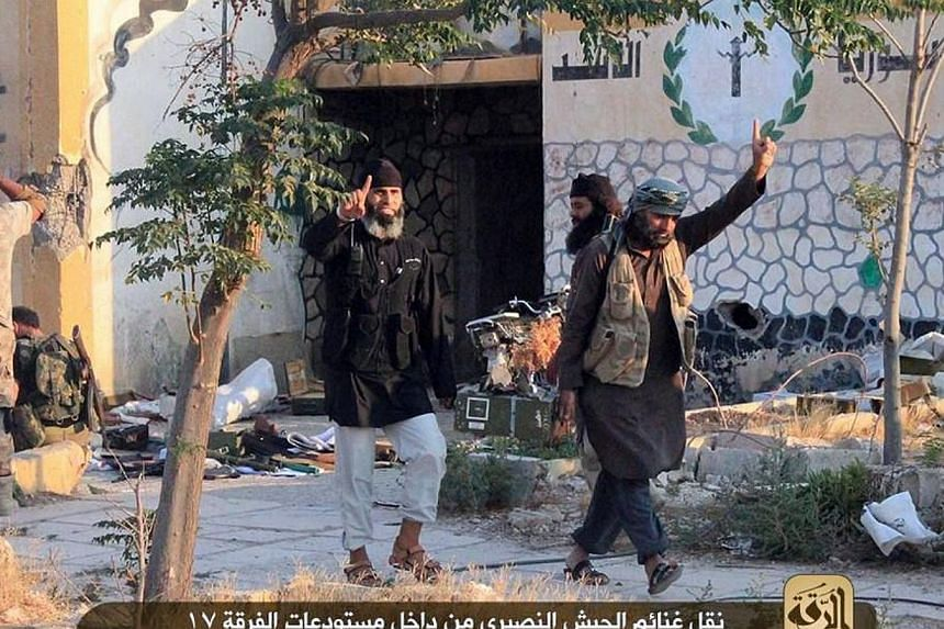 An image made available by militant media outlet Welayat Raqa on July 25, 2014, allegedly shows members of the Islamic State extremist group raising their index fingers, as they loot ammunition from a Syrian army base in the northern rebel-held Syria