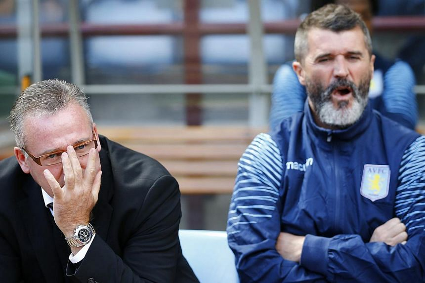 Aston Villa manager Paul Lambert (left) and his assistant Roy Keane sit in the dugout before their English Premier League soccer match against Newcastle United at Villa Park in Birmingham, central England Aug 23, 2014. Keane's war of words with Alex
