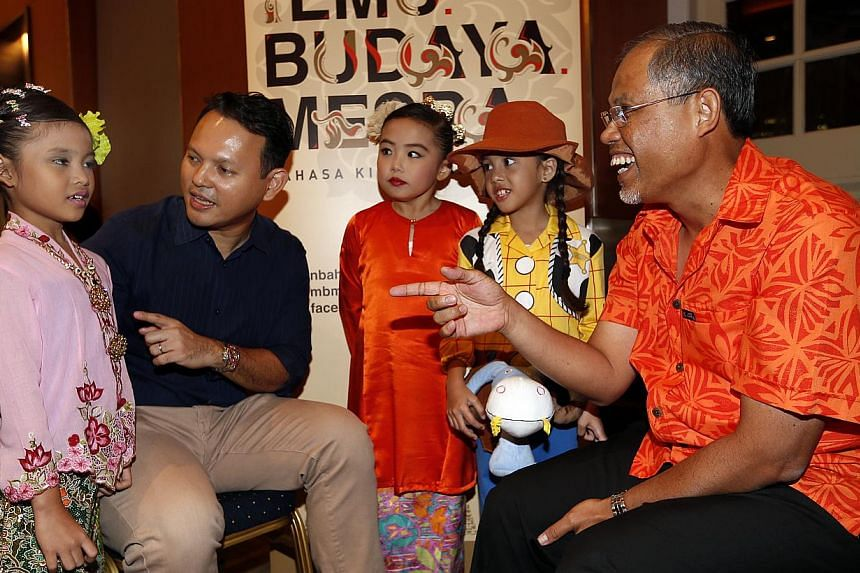 Mr Zaqy Mohamad, (second, left), chairman of the organising committee of Malay Language month and Mr Masagos Zulkifli, (right), chairman of the Malay Language Council, interacting with Putri Emily Muhammad Joehadi,7, (in light purple), Seri Emaryana