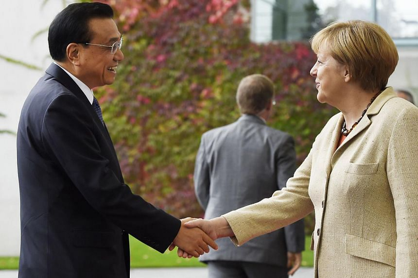 German Chancellor Angela Merkel (right) shakes hands with Chinese Prime Minister Li Keqiang upon his arrival at the Chancellery in Berlin on Oct 9, 2014. -- PHOTO: AFP