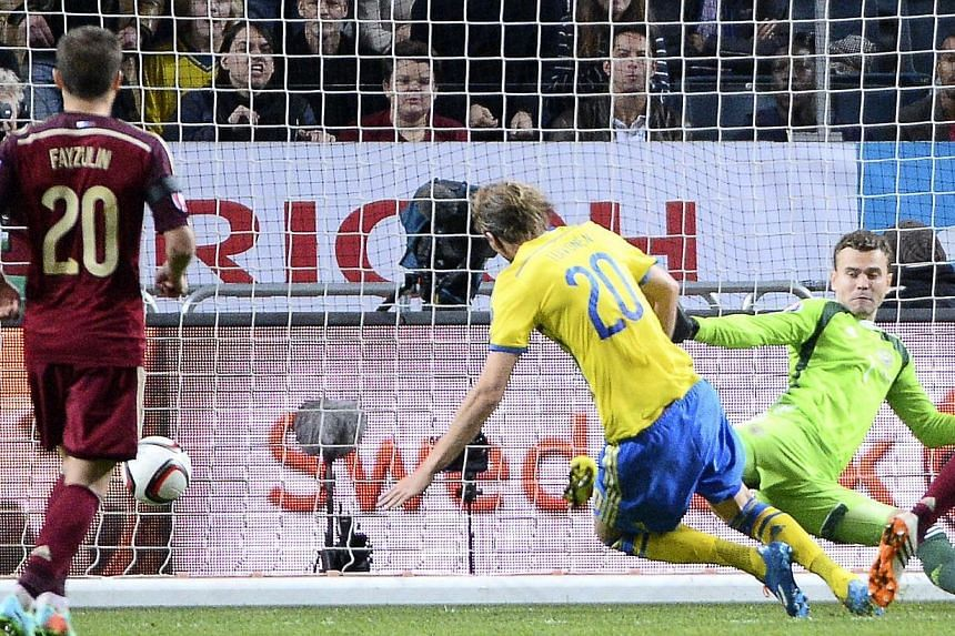 Sweden's forward Ola Toivonen scores past Russia's goalkeeper Igor Akinfeev on Oct 9, 2014 at Friends Arena in Solna, near Stockholm during the Euro 2016 qualifying football match between Sweden and Russia. -- PHOTO: AFP