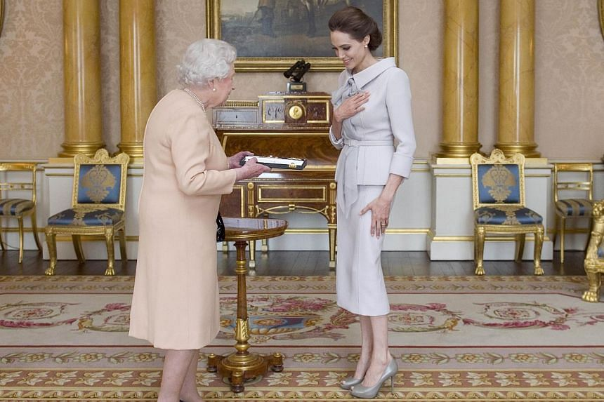 Actress Angelina Jolie (right) is presented with the Insignia of an Honorary Dame Grand Cross of the Most Distinguished Order of St Michael and St George, by Britain's Queen Elizabeth in the 1844 room at Buckingham Palace in London on Oct 10, 2014. -
