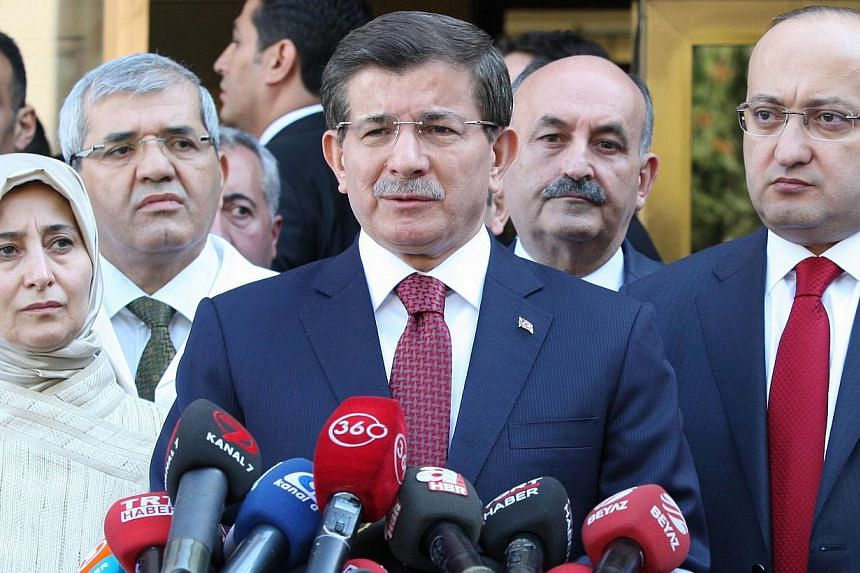 Turkish Prime Minister Ahmet Davutoglu (centre) gives a press conference after visiting the security members injured last night on the sideline of Kurds protests over the government's policy on Islamic State (IS) militants in southeastern Turkey, on