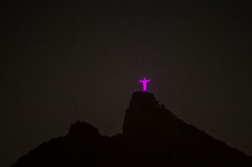 The Christ the Redeemer statue atop Corcovado hill is lit up in pink to promote worldwide Breast Cancer Awareness Month in Rio de Janeiro, Brazil, on Oct 10, 2014. -- PHOTO: AFP