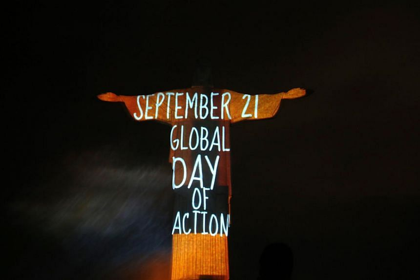 The statue of Christ the Redeemer is lit up with a message announcing a global mobilisation for climate change, in Rio de Janeiro on Sept 18, 2014. -- PHOTO: REUTERS