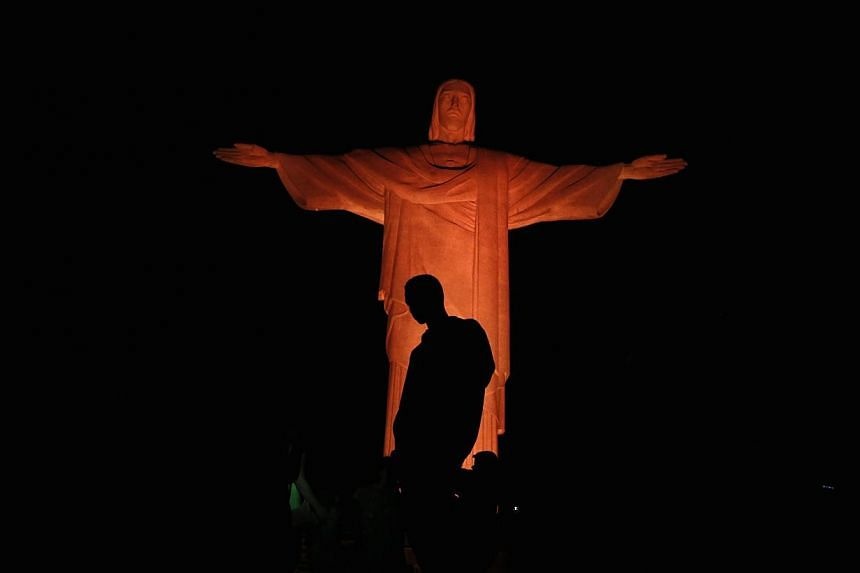 A man stands in front of the statue of Christ the Redeemer as it is lit up in orange to commemorate the Day against Human Trafficking and Missing Persons, celebrated by the Archdiocese of Rio de Janeiro on Sept 10, 2014. -- PHOTO: REUTERS