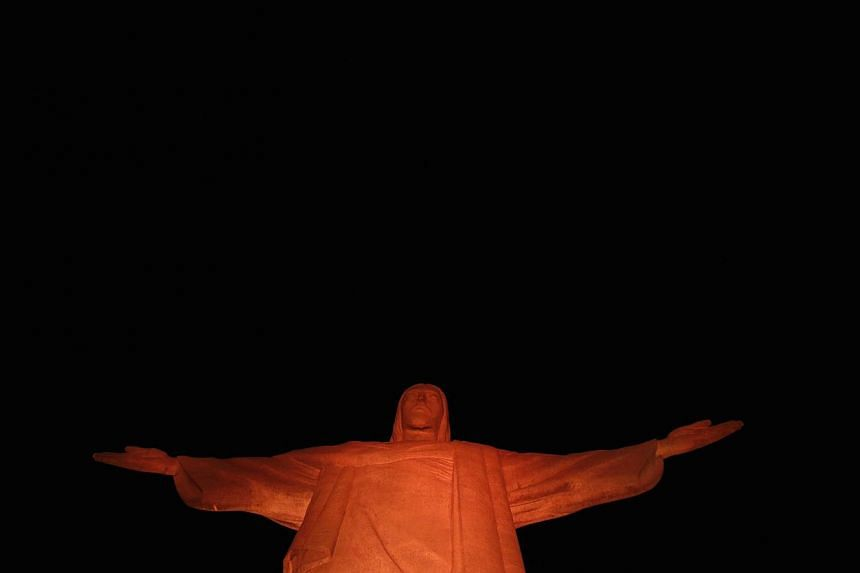 The statue of Christ the Redeemer is pictured lit up in orange to commemorate the day against Humans Trafficking and Missing Persons, celebrated by the Archdiocese of Rio de Janeiro on Sept 10, 2014. -- PHOTO: REUTERS
