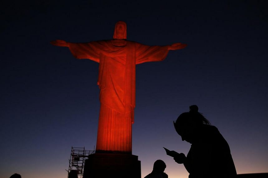 People stand in front of the statue of Christ the Redeemer as it is lit up in orange to commemorate the Day against Human Trafficking and Missing Persons, celebrated by the Archdiocese of Rio de Janeiro on Sept 10, 2014. -- PHOTO: REUTERS