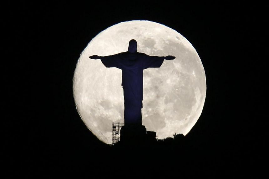 The supermoon is pictured behind the Christ the Redeemer statue in Rio de Janeiro on Aug 11, 2014. Occurring when a full moon or new moon coincides with the closest approach the moon makes to the Earth, the supermoon results in a larger-than-usual ap