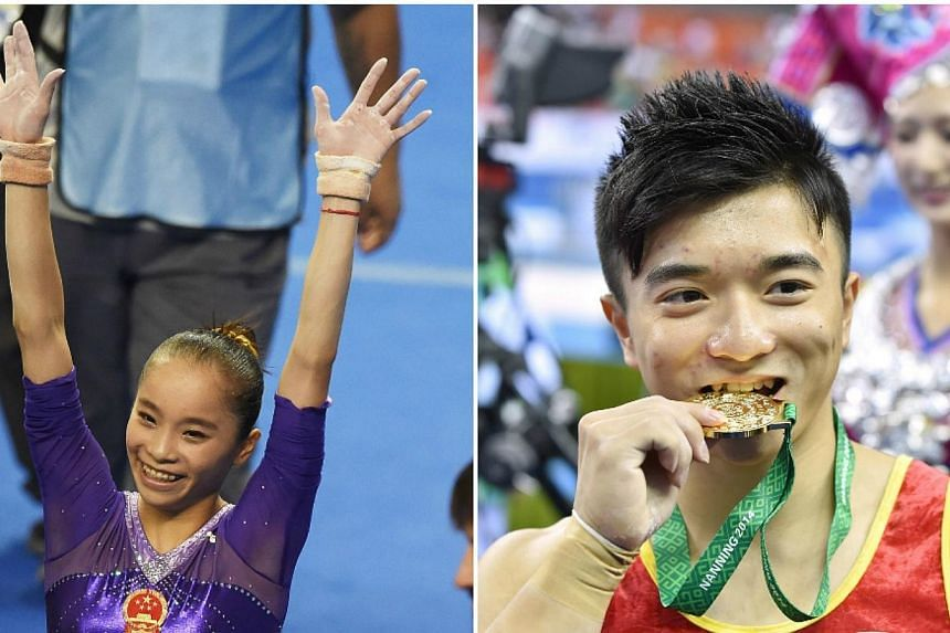 China's Yao Jinnan (left) and Liu Yang celebrate after winning the women's uneven bars final and men's rings final respectively at the gymnastics world championships in Nanning on Oct 11, 2014. -- PHOTO: AFP