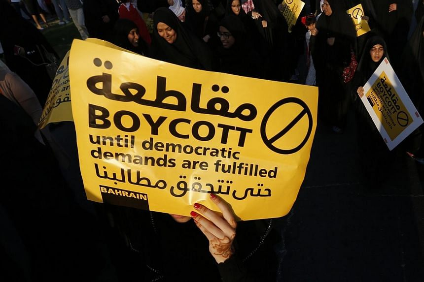 A protester holding a sign marches during a rally organised by Bahrain's main opposition party Al Wefaq in Budaiya, west of Manama, Bahrain on Sept 19, 2014.Bahrain's Shi'ite-led opposition on Saturday announced a boycott of parliamentary