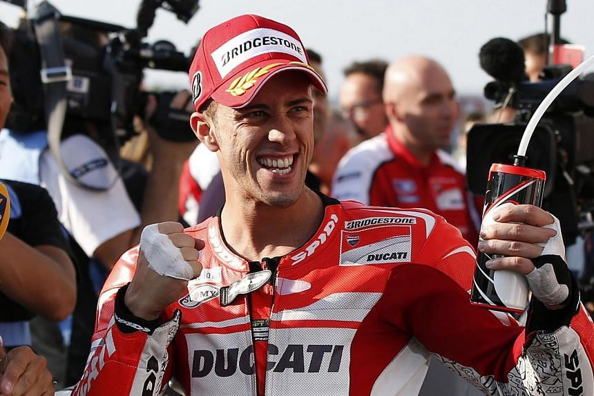 Ducati MotoGP rider Andrea Dovizioso of Italy celebrates after winning the pole position for Sunday's Japanese Grand Prix during a qualifying session at the Twin Ring Motegi circuit in Motegi, north of Tokyo on Oct 11, 2014. -- PHOTO: REUTERS