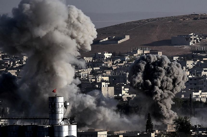 Smoke rises after strikes from the US-led coalition in the Syrian town of Ain al-Arab, known as Kobane by the Kurds, in the south-eastern village of Mursitpinar, Sanliurfa province, on Oct 10, 2014. -- PHOTO: AFP
