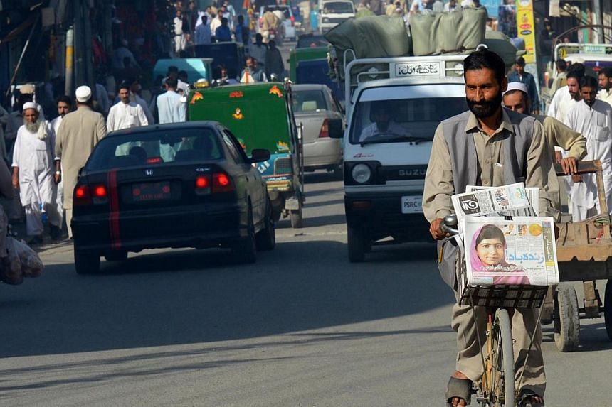 A Pakistani vendor carries morning newspapers with the headline of Nobel Peace Prize winner, child education activist Malala Yousafzai on his bicycle in Malala's hometown Mingora in north-western Swat valley on Oct 11, 2014. -- PHOTO: AFP