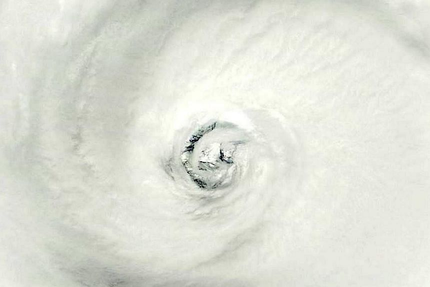 This October 10, 2014, satellite image from NASA shows the eye of Super Typhoon Vongfong in the Philippine Sea. The Joint Typhoon Warning Center predicts landfall around October 12, 2014 at 23:00 UTC near Sasebo, Japan. -- PHOTO: AFP