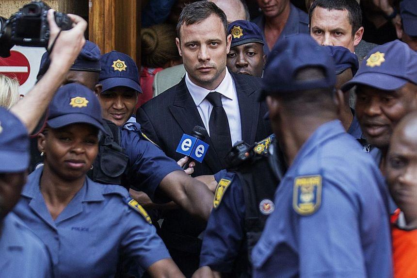 South African Paralympian athlete Oscar Pistorius (centre) leaves the High Court in Pretoria on Sept 12, 2014 after the verdict in his murder trial where he was found guilty of culpable homicide. -- PHOTO: AFP