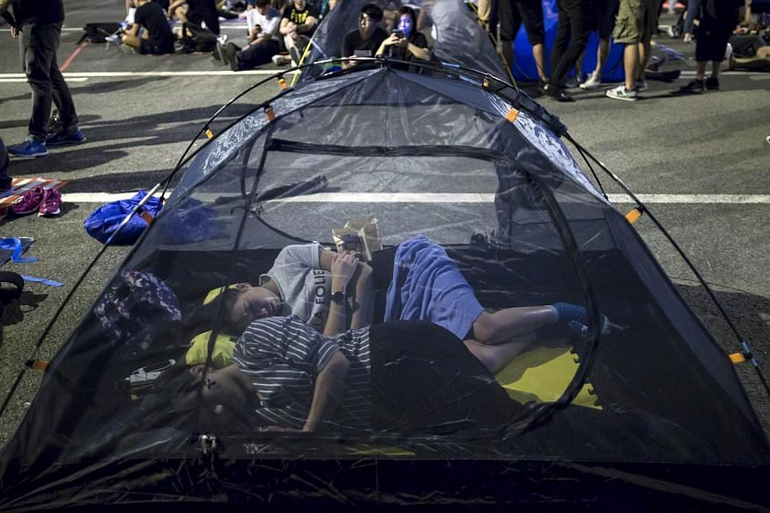 Protesters of the Occupy Central movement sleep in a mosquito tent as pro-democracy protesters continue blocking areas around the government headquarters building in Hong Kong on Oct 11, 2014. -- PHOTO: REUTERS