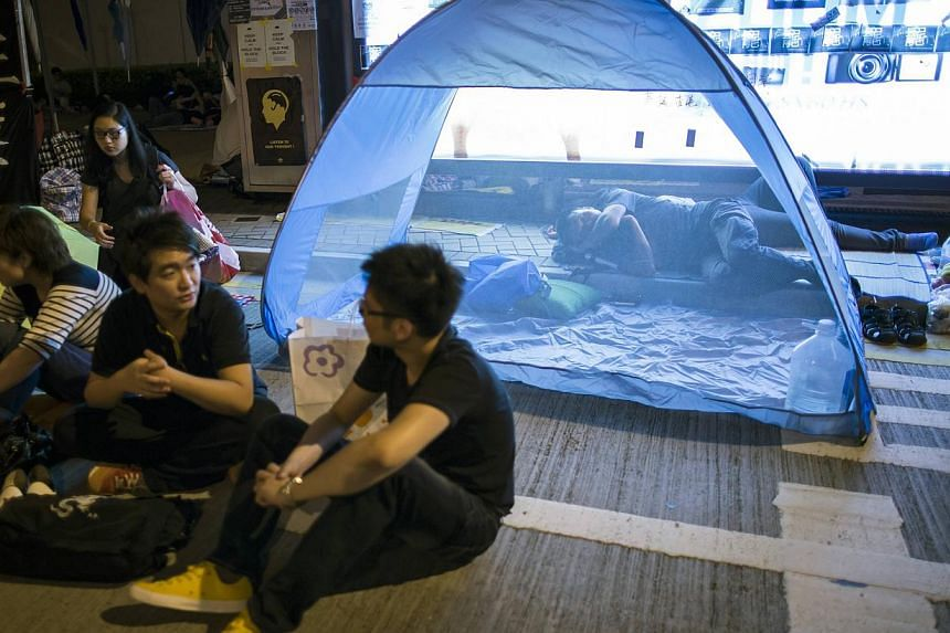A protester of the Occupy Central movement sleeps in a tent as pro-democracy protesters continue blocking areas around the government headquarters building in Hong Kong on Oct 11, 2014. -- PHOTO: REUTERS