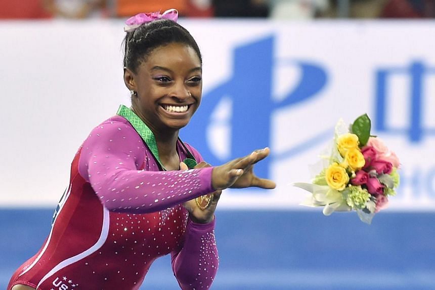 Winner Simone Biles of the US throws a bouquet as she reacts against a bee during the awards ceremony of the women's all-around final at the gymnastics world championships in Nanning on Oct 10, 2014. -- PHOTO: AFP