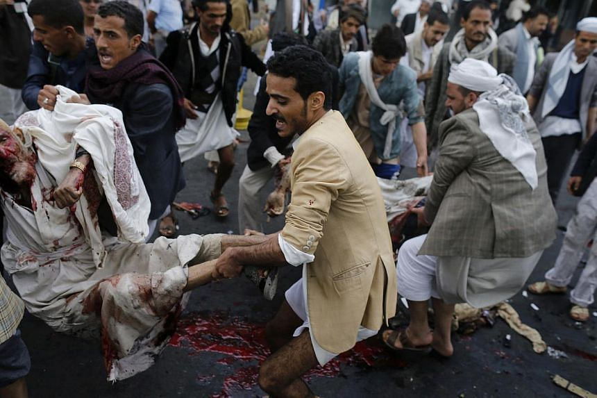 Shi'ite Houthi rebels carry wounded men after a suicide attack in Sanaa Oct 9, 2014. Al-Qaeda's wing in Yemen on Friday claimed responsibility for a suicide bomb attack on Yemen's powerful Shi'ite Houthi group that killed at least 47 people. --