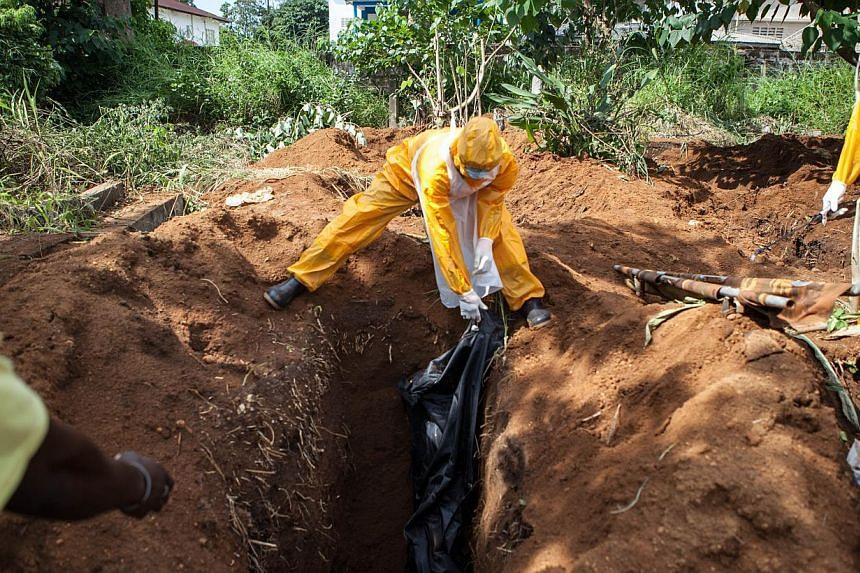 A team of funeral agents specialised in the burial of victims of the Ebola virus put a body in a grave at the Fing Tom cemetery in Freetown, Sierra Leone on Oct 10, 2014. Pledges of financial aid to fight Ebola have fallen far short of the US$1 billi