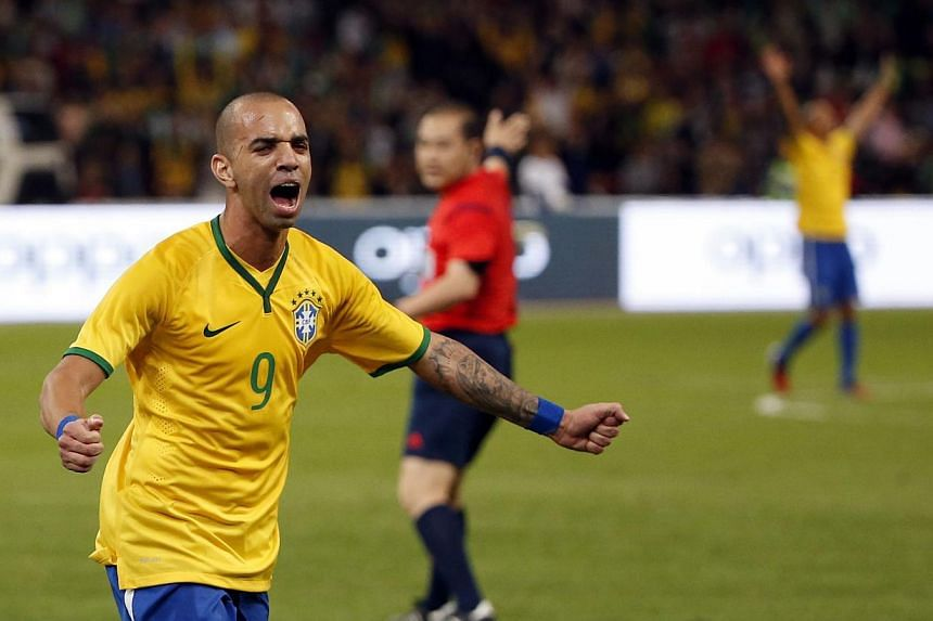 Brazil's Diego Tardelli celebrates after scoring a first goal against Argentina during the international friendly soccer match titled 'The Super Classic of the Americas' at the National Stadium, or the Bird's Nest, in Beijing,China on Oct 11, 2014. -