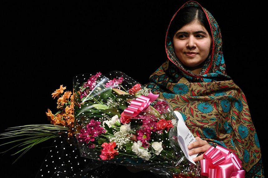 Pakistani rights activist Malala Yousafzai holds a bouquet of flowers after addressing the media in Birmingham, central England on Oct 10, 2014.Malala will travel to Canada to become an honorary citizen, Prime Minister Stephen Harper said Frida