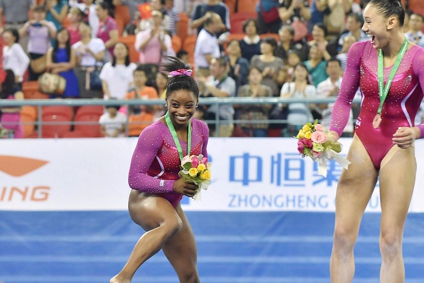 Winner Simone Biles of the US (left) reacts as a bee buzzes past during the awards ceremony of the women's all-around final at the gymnastics world championships in Nanning on Oct 10, 2014. On the right is second placed Kyla Ross of the US. -- PHOTO:
