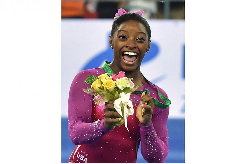 Winner Simone Biles of the US reacts as a bee (top right) buzzes past during the awards ceremony of the women's all-around final at the gymnastics world championships in Nanning on Oct 10, 2014. -- PHOTO: AFP