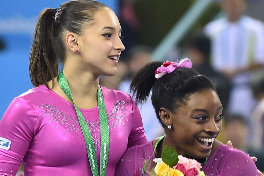 Winner Simone Biles of the US (right) and second placed Larisa Andreea Iordache of Romania react to a bee buzzing past during the awards ceremony of the women's all-around final at the gymnastics world championships in Nanning on Oct 10, 2014. -- PHO
