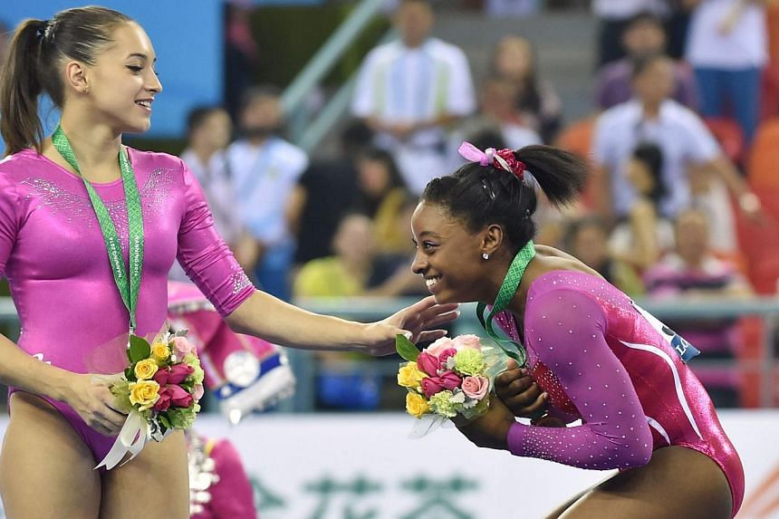 Winner Simone Biles of the US (right) and second placed Larisa Andreea Iordache of Romania react from a bee buzzing past during the awards ceremony of the women's all-around final at the gymnastics world championships in Nanning on Oct 10,