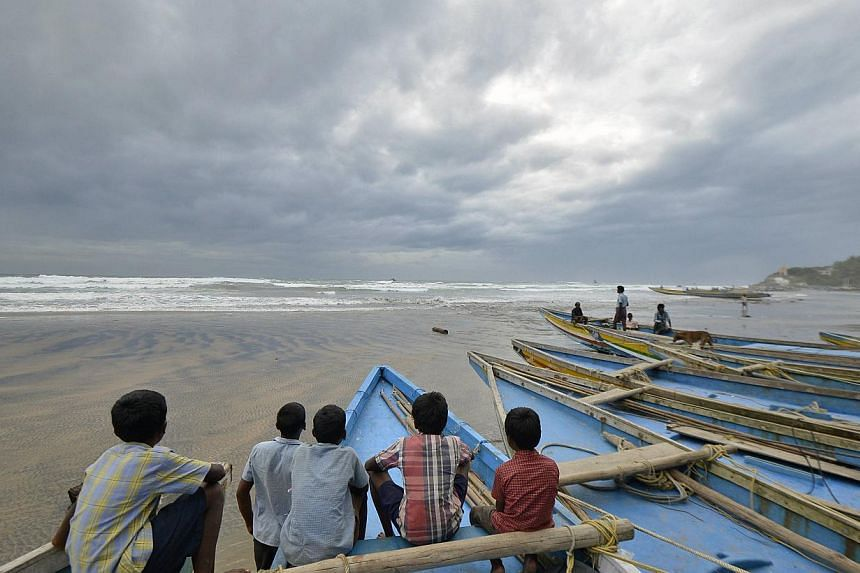 Children sit on fishing boats by the shore before being evacuated, at Visakhapatnam district in the southern Indian state of Andhra Pradesh on Oct 11, 2014. -- PHOTO: REUTERS