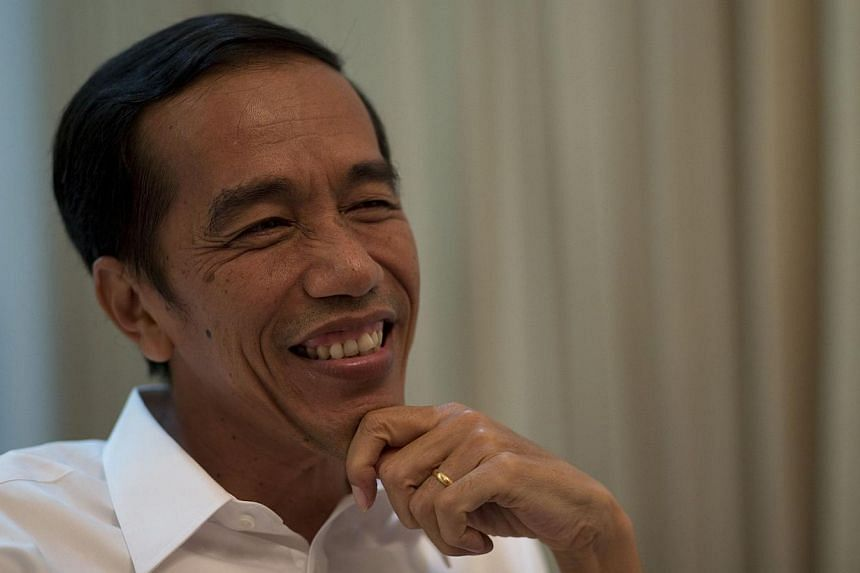Indonesia's President-elect Joko Widodo, seen here (above) in July, on Friday sought to reassure Indonesians and foreign investors that his relationship with parliament over the next five years will be one of cooperation, not antagonism. -- PHOT