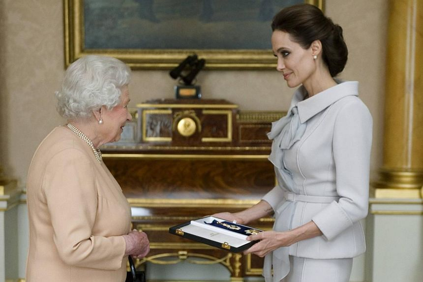 Actress Angelina Jolie is presented with the Insignia of an Honorary Dame Grand Cross of the Most Distinguished Order of St Michael and St George, by Britain's Queen Elizabeth II in the 1844 room at Buckingham Palace in London on October 10, 2014. --
