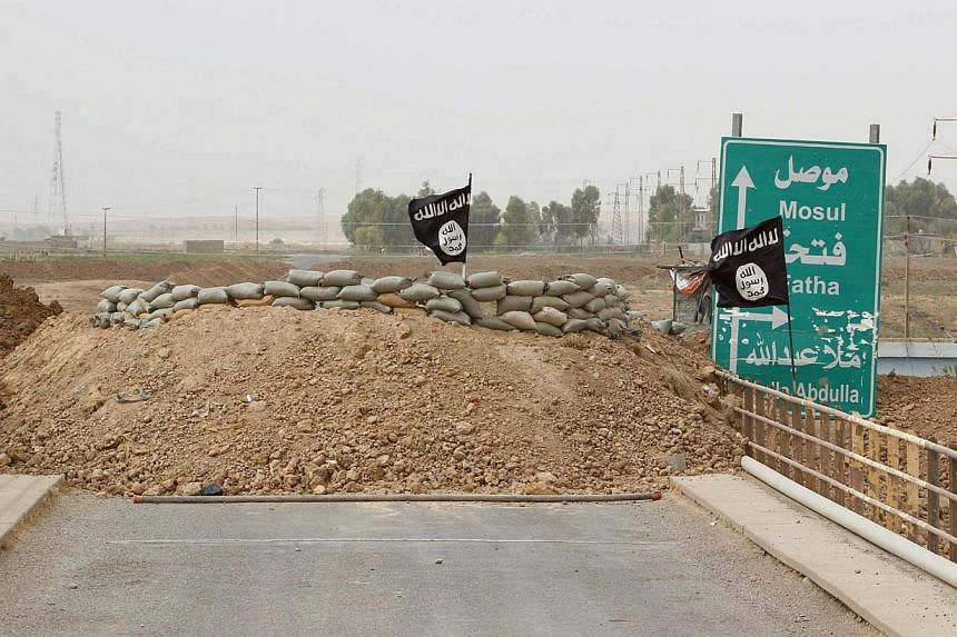 Islamic State flags flutter on the Mullah Abdullah bridge in southern Kirkuk Sept 29, 2014.Islamic State group fighters executed nine people on Friday in two northern Iraqi towns on suspicion of ties to anti-militant Sunni grassroots organisati