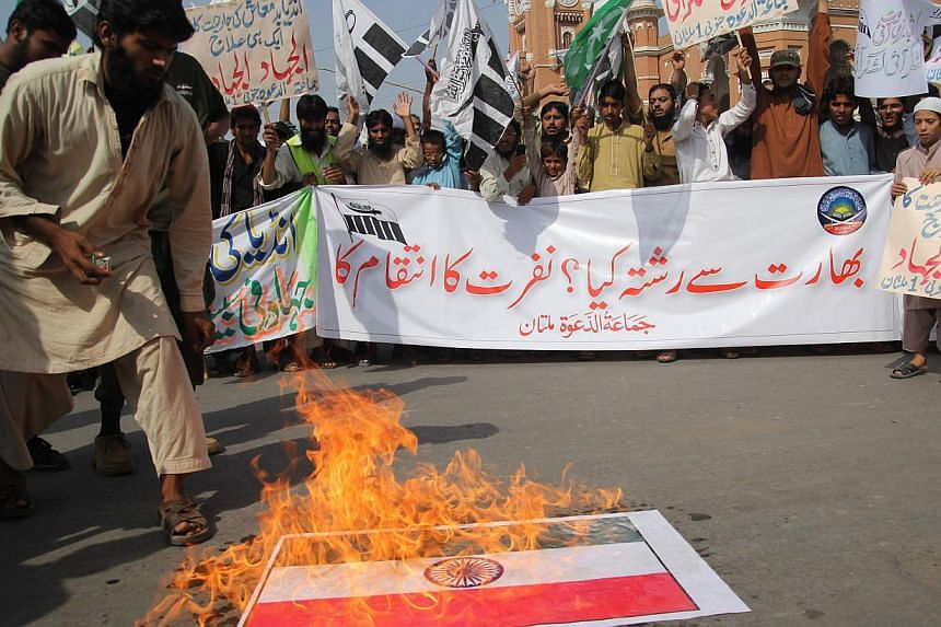 A Pakistani activist of the Islamic hardline organisation Jamaat ud Dawa (JuD) torches an Indian flag during a demonstration in Multan on Oct 10, 2014.At least seven people were killed and 42 hurt in a stampede during an anti-government protest