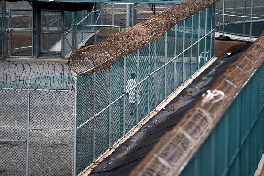 """An April 8, 2014 file photo made during an escorted visit and reviewed by the US military shows an unidentified detainee walking in the excercise yard of the """"Camp 6"""" detention facility at the US Naval Station in Guantanamo Bay, Cuba.President"""