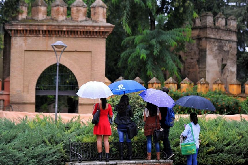 Tourists try to peer over a fence at Los Jardines de Murillo that is to be one of the sets for the fifth season of the series Game Of Thrones at the Reales Alcazares (Royal Palace) in Sevilla on Oct 10, 2014. Film crews began shooting part of the fif