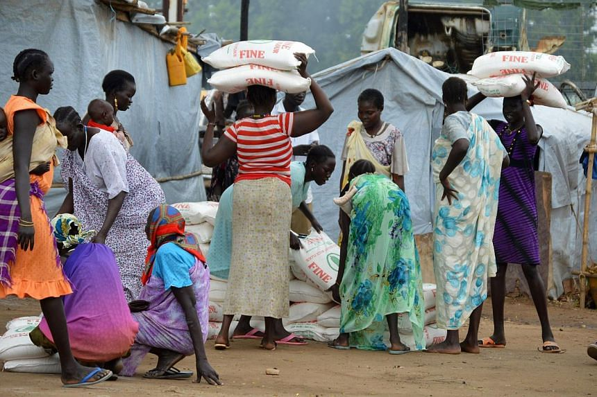 Women carry maize flour sacks during food distribution by the Catholic Church to refugees and displaced people in Juba on Aug 30, 2014.The levels of rape in war-torn South Sudan are the worst the UN special envoy on sexual violence has ever see