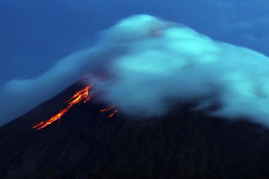 Lava flows from the crater of Mayon volcano as seen from Legazpi City, Albay province, south-east of Manila on Sept 17, 2014.A fresh flow of lava from Mayon on Sunday, Oct 12, 2014, has raised fears the Philippines' most active volcano will eru